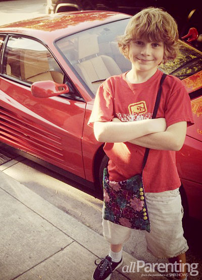 Young confident boy with flower purse by sports car