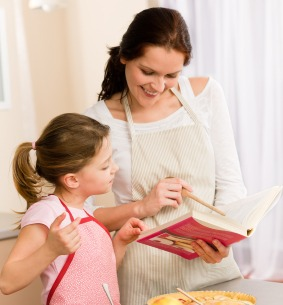 mother and daughter reading cookbook