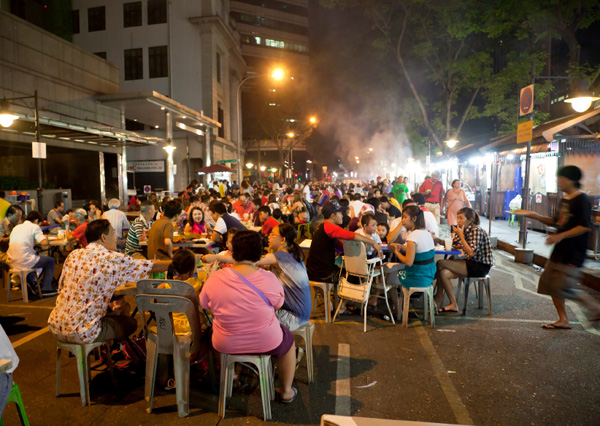 People eating satay in Singapore at night
