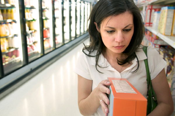 Woman examining nutrition information from cereal box in supermarket aisle