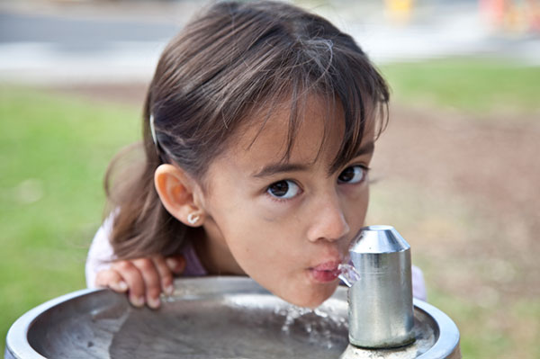 Little girl drinking water from fountain