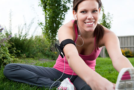 Woman listening to music while stretching