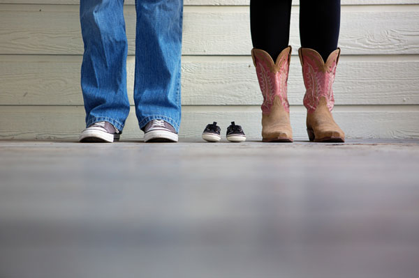 A man, a woman and baby shoes pregnancy announcement