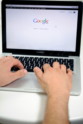 man searching Google on laptop
