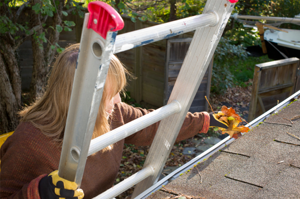 Woman cleaning gutters