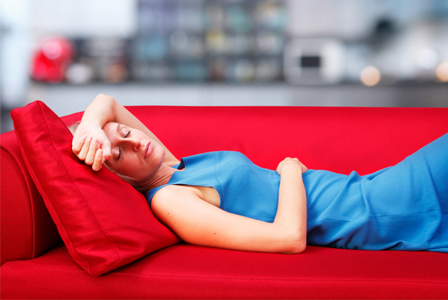 Tired woman laying on couch