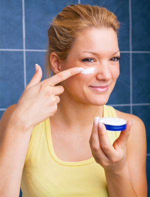 Woman putting lotion under eyes