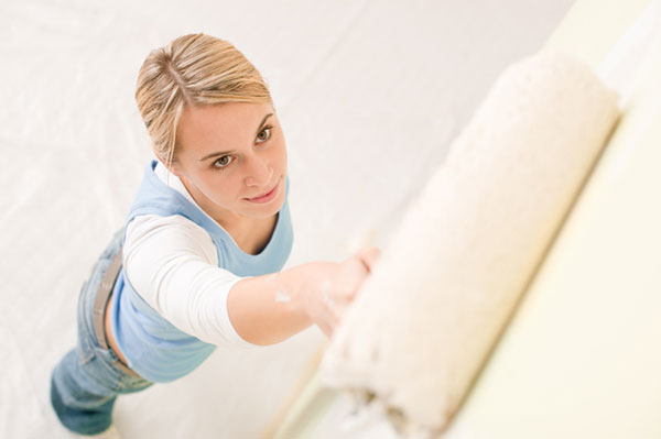 Woman painting walls in her house | Sheknows.com