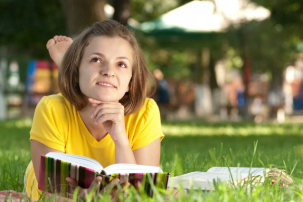 Teen girl reading outdoors