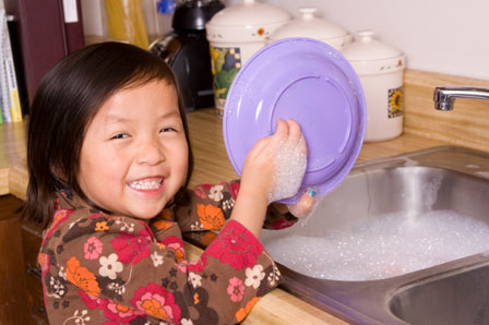 Young girl washing dishes