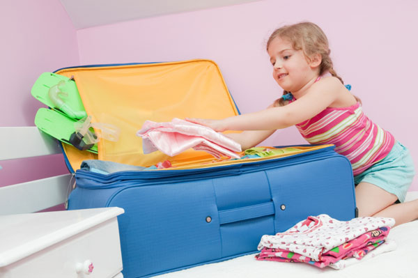 Little girl packing for vacation