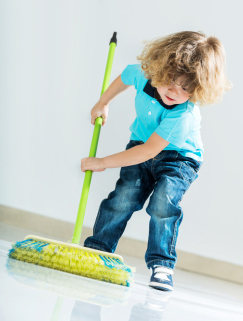 young boy sweeping the floor