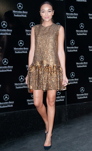 Ashley Madekwe wearing a gold drop waist dress to NYFW
