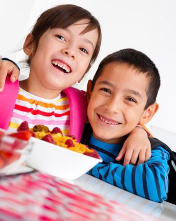 Happy siblings having breakfast before school