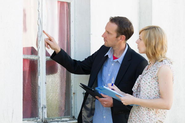 Man and woman inspecting house