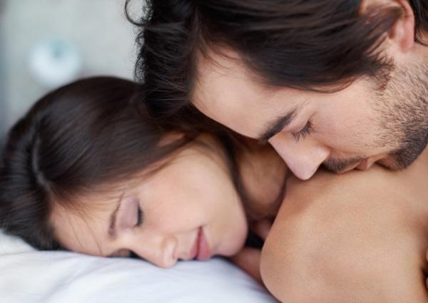 Man kissing a woman's shoulders