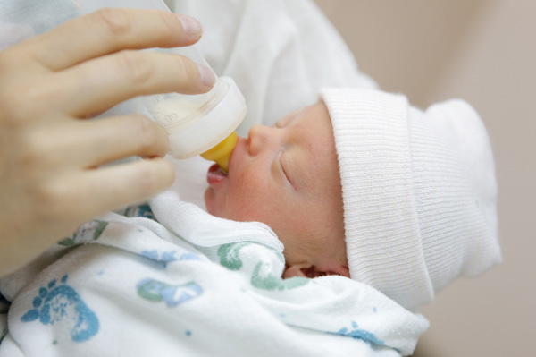 Mother bottle feeding newborn