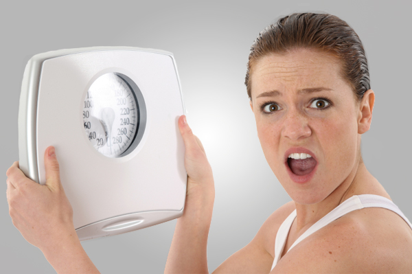 Surprised woman holding up a scale