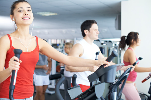 Woman using elliptical at gym