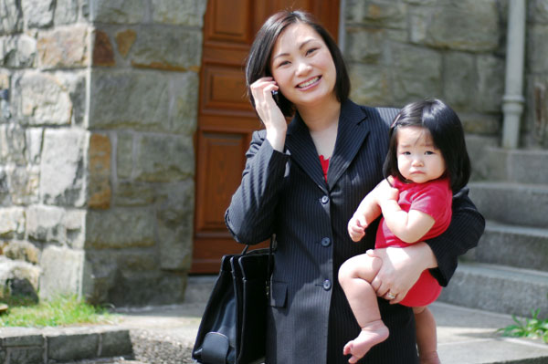 Working mom on phone while carrying baby