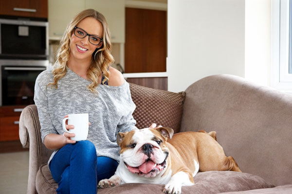 Woman with bulldog on couch