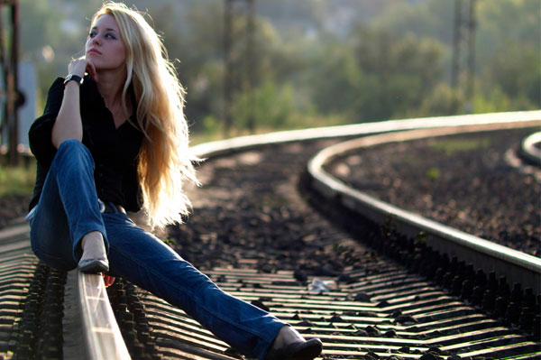 Woman in blue jeans sitting on train track
