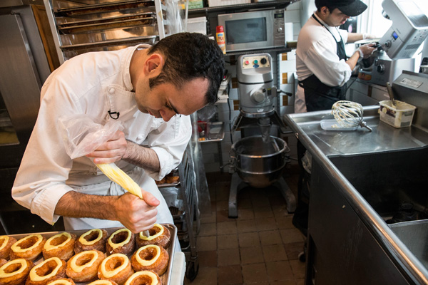 Chef Dominique Ansel prepares a tray of cornets at Dominique Ansel Bakery on June 10, 2013 in New York City