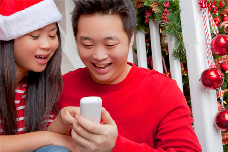 Happy couple on phone on Christmas