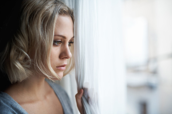 Sad woman looking out window