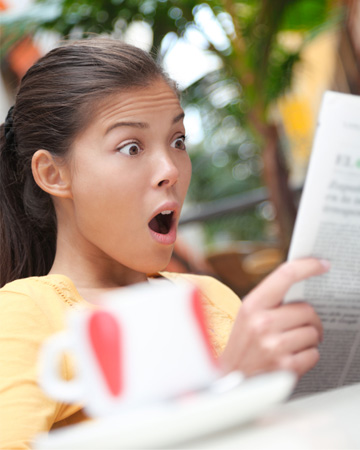 Shocked woman reading newspaper