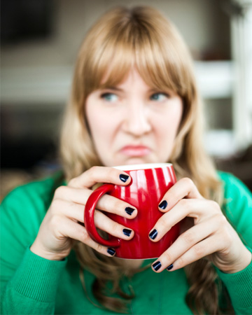 Woman drinking a bad cup of coffee