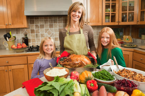Mom cooking Thanksgiving dinner with daughters