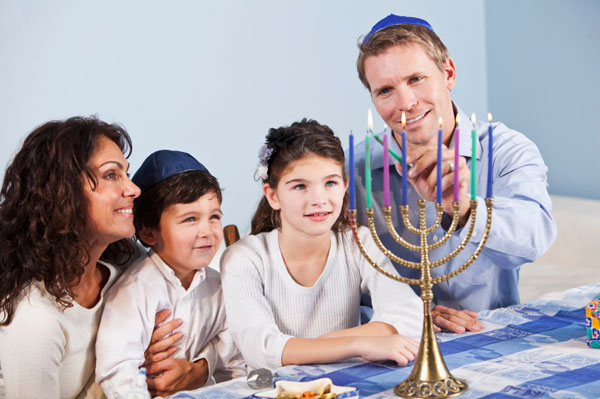 Family lighting the menorah for Hanukkah