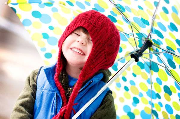 Happy young boy playing in the rain