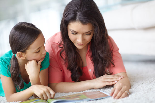 Mother and daughter reading magazine together
