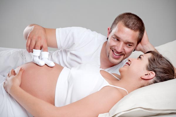 Pregnant woman in bed with man