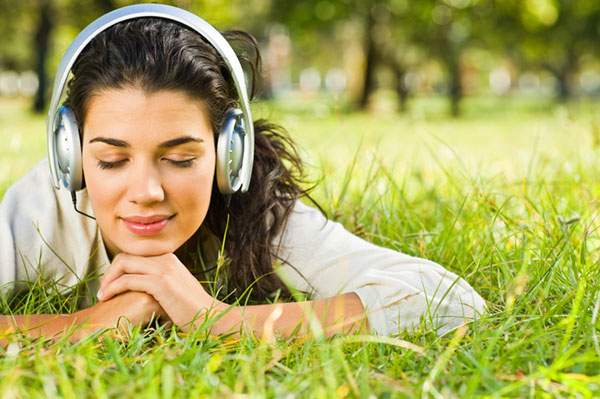 Woman using headphones | Sheknows.com