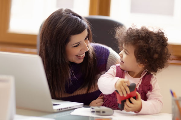 Woman working and playing with child | Sheknows.com