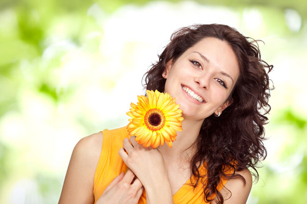 Smiling woman holding a sunflower | Sheknows.com
