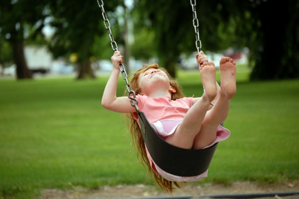 Girl pumping on a swing