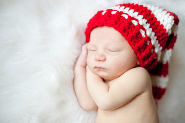 Sleeping newborn wearing Santa hat