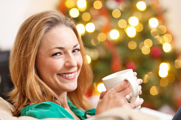 Woman drinking tea by the Christmas tree
