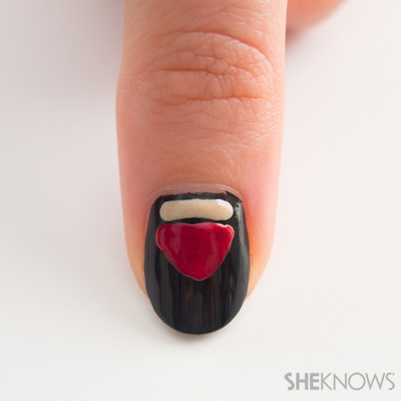Paint a tan line across the top of the thumb nail and a red triangle beneath it. Let the paint dry and then paint two 'v' shapes on the tan line and some black lines coming in to create an ornate shape. Add three tan drops in the middle of the red design.