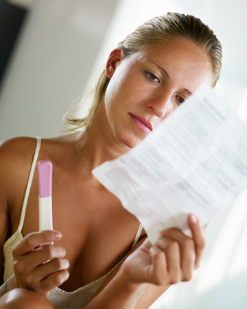 Confused woman with pregnancy test