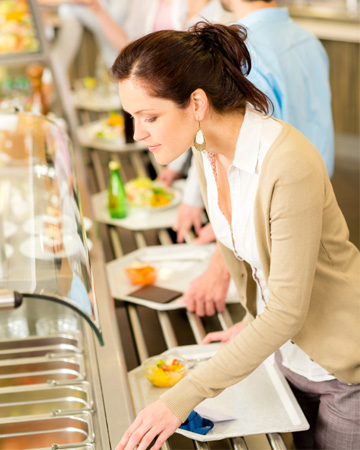 Woman selecting food in a cafeteria