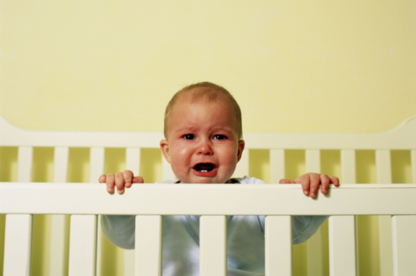 Baby crying in crib | PregnancyAndBaby.com
