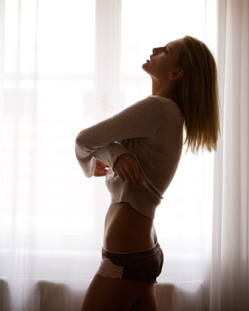 Woman undressing in front of window