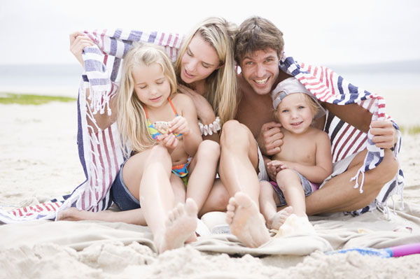 Family on beach with blanket