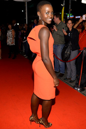 Lupita Nyong'o wearing orange sheath dress