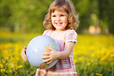 Young girl holding globe | Sheknows.com